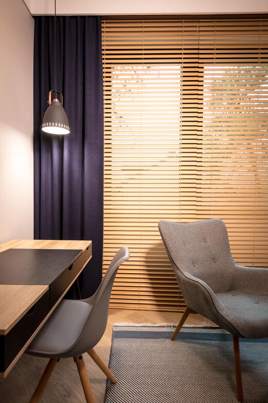 drewniane żaluzje okienne Anwis jako tło dla szarego fotela wgabinecie