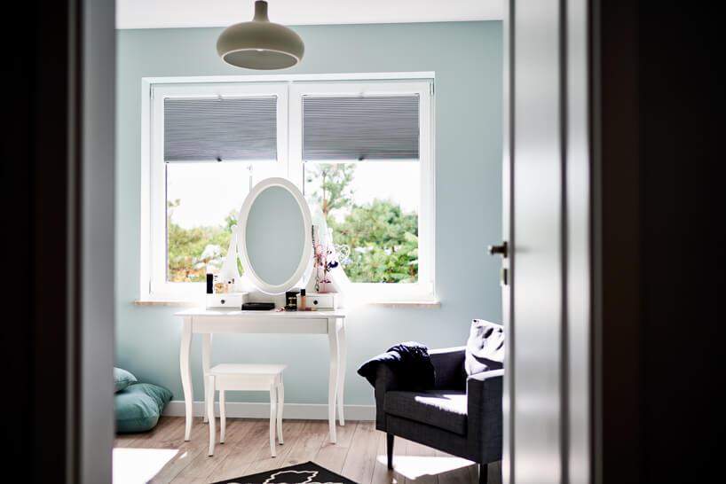 nowoczesne plisowane szare żaluzje okienne od ANWIS nad biała toaletką zowalnym lustrem