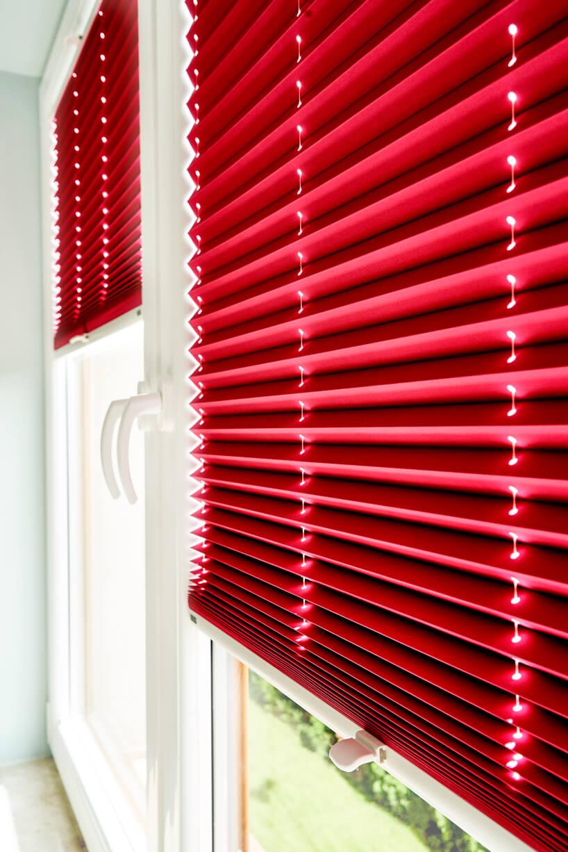 nowoczesne plisowane czerwone żaluzje okienne od ANWIS wbiałym oknie zbliska
