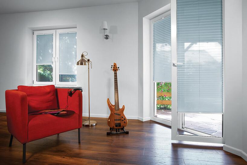 niebieskie plisowane żaluzje ANWIS wdwóch oknach wbiałym salonie zdrewnianą podłogą igitara na stojaku obok czerwonego fotela