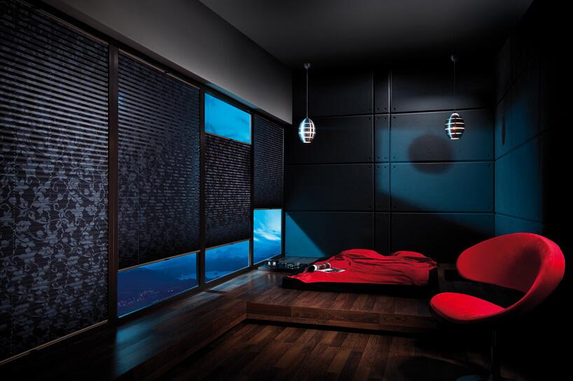 ciemne plisowane żaluzje ANWIS zmotywem roślinnym wciemnym salonie zciemną drewnianą podłogą