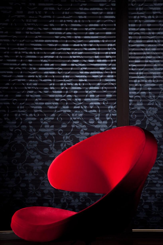 ciemne plisowane żaluzje ANWIS zmotywem kwiatowym jako tło dla czerwonego fotela