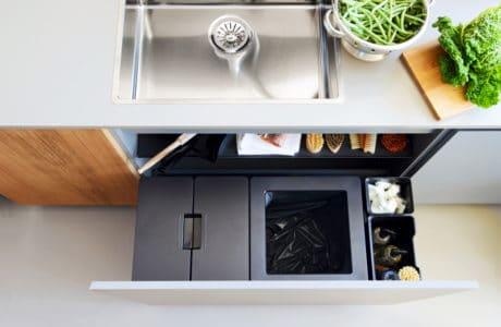 wysuwany kosz z szafki kuchennej z drewnianym frontem i białym blatem