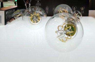 trzy żarówki LED leżące na białym podświetlonym blacie