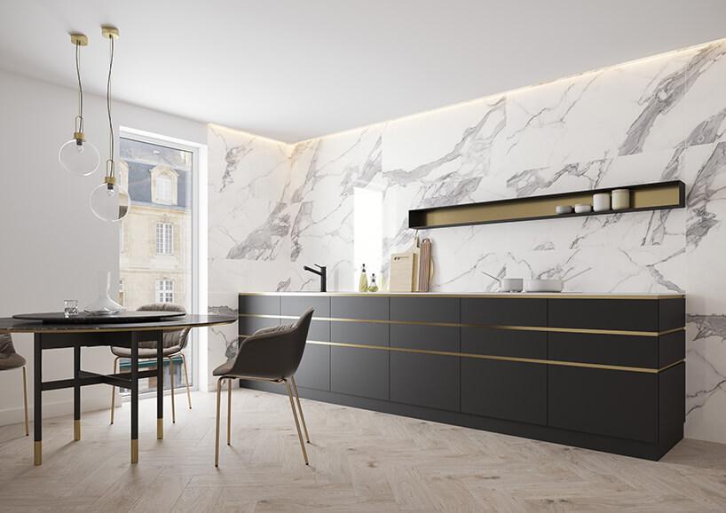 elegancka biała kuchnia zkamiennymi białym płytami na ścianie ze czarnym meblami kuchennymi ze złotymi wstawkami