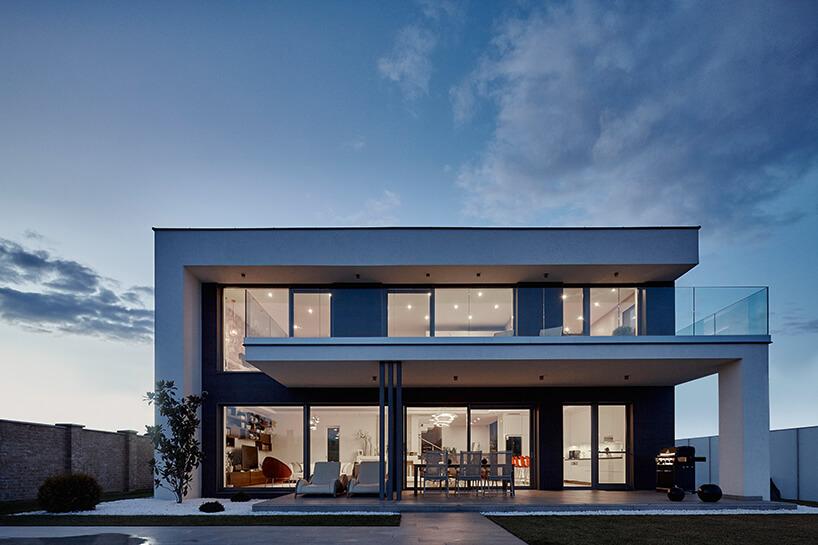 nowoczesnym dom wieczorem zwysokimi oknami