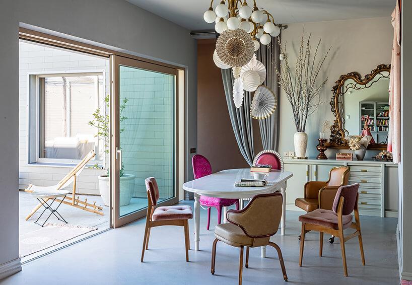 elegancki salon zprzestronnymi szklanymi drzwiami suwanymi zbiałym stołem zrożnymi różowymi fotelami