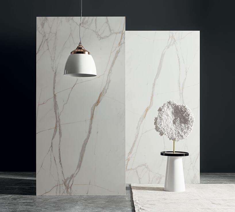 biało miedziana lampa wisząca na tle białej kamiennej ścianki