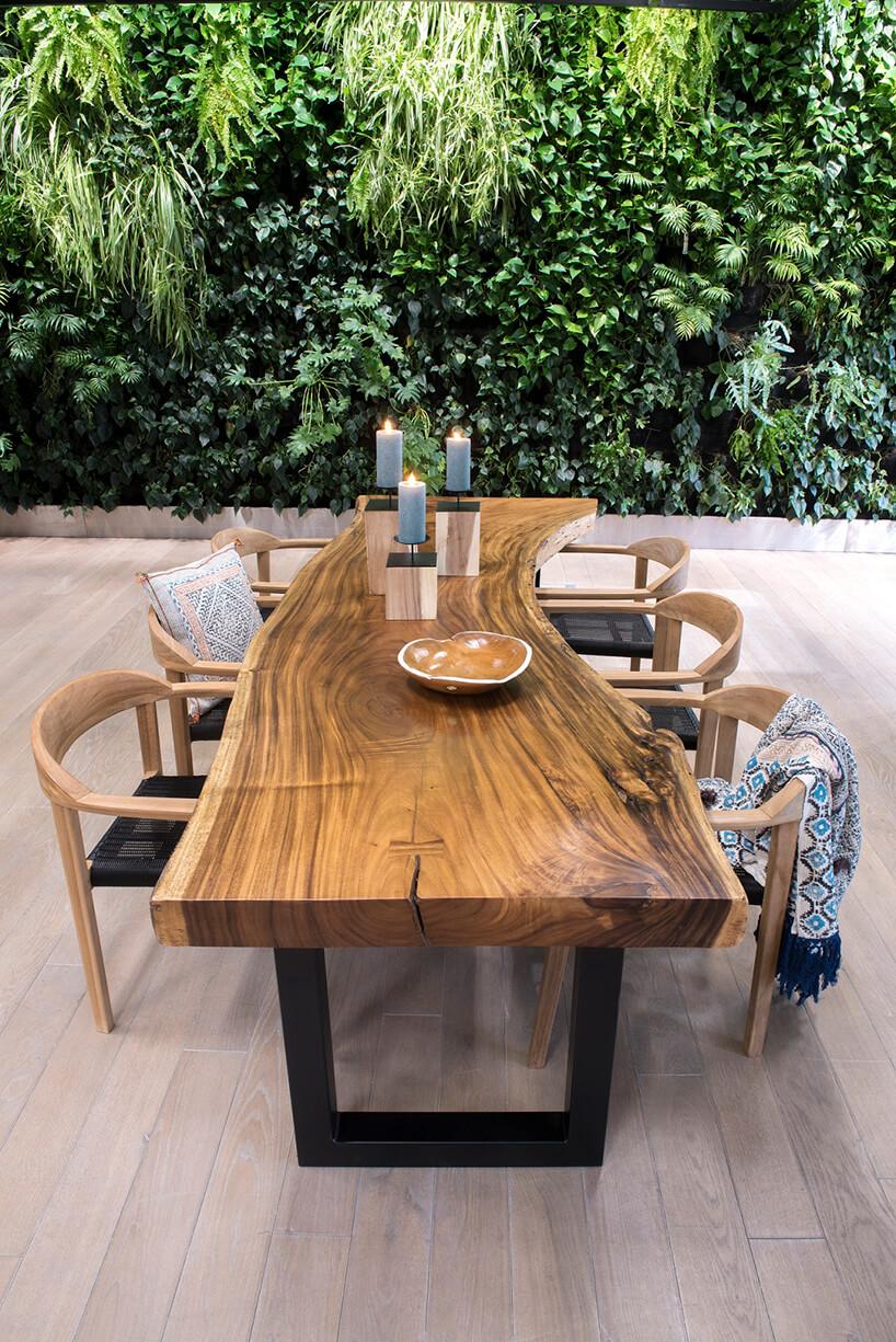 drewniany stół ze słojami na czarnej ramie zkrzesłami obok