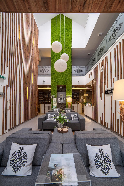 recepcja zszarymi siedziskami izieloną ścianą wBacówka Radawa & SPA