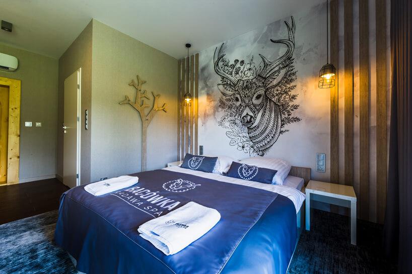 pokój hotelowy wBacówka Radawa & SPA dużymi łóżkiem igrafiką jelenia na ścianie