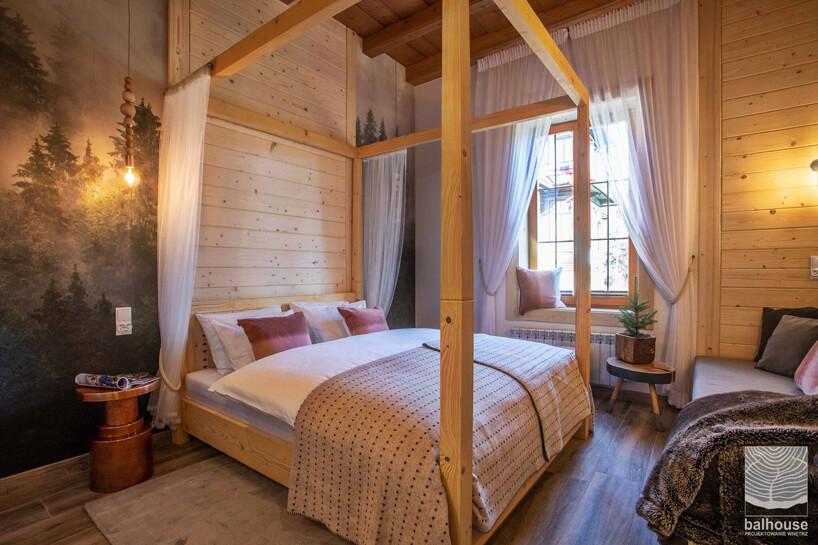pokój hotelowy wdrewnie zdużym łóżkiem zbaldachimem