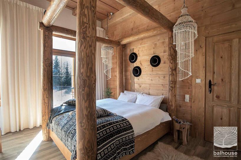 pokój hotelowy wdrewnie wstylu góralskim zdużym łóżkiem