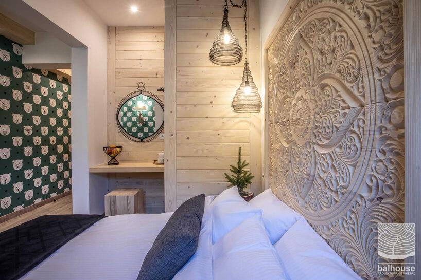 pokój hotelowy zdrewnianymi zdobieniami na ścianie wNiedźwiedzia Residence