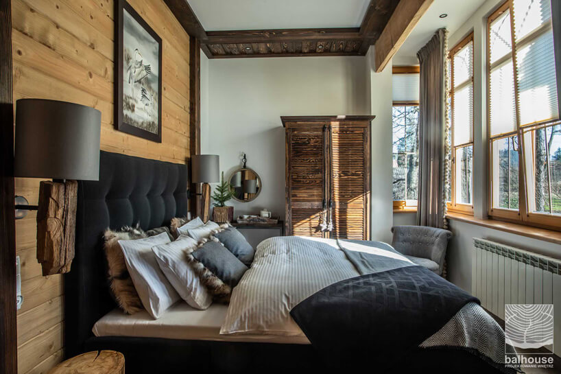 pokój hotelowy zdużym łóżkiem na wprost przeszklonej ściany wNiedźwiedzia Residence