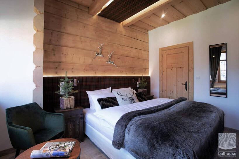 pokój wNiedźwiedzia Residence dużymi łóżkiem na tle grubych bali drewnianych
