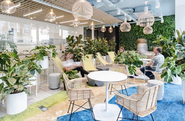 zielona nowocześnie urządzona przestrzeń socjalna w open space biurowca