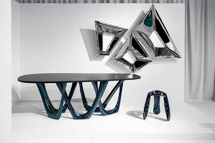 mały metalowy stołek obok chromowanej konstrukcji na ścianie