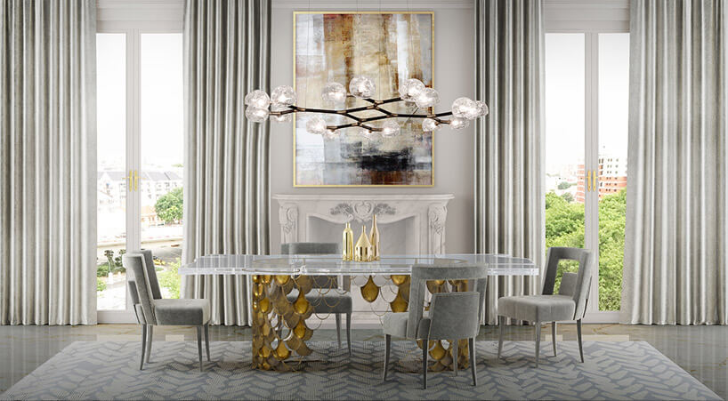 stół zkrzesłami wjasno-szarym wnętrzu pod dużym żyrandolem