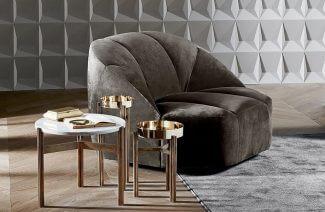 szary fotel obok stolików ze złotymi nogami na tle szarej ściany 3d