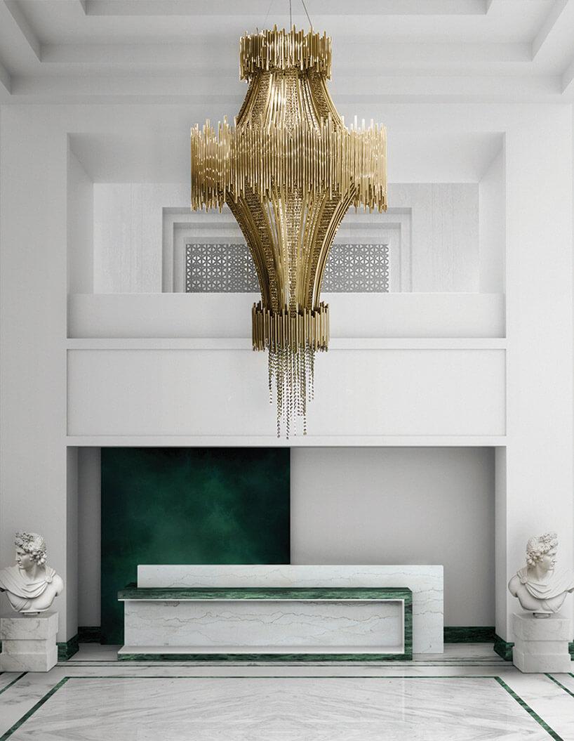 białe wnętrze zzielonymi akcentami iduży złoty żyrandolem