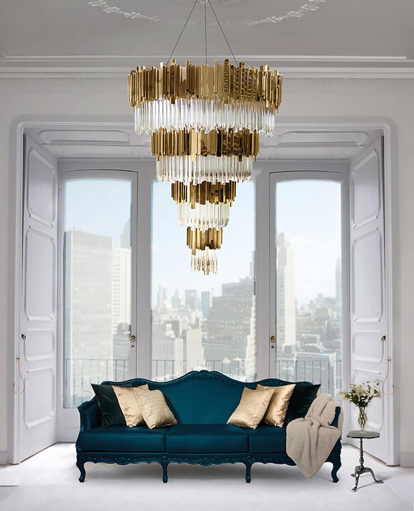 niebieska sofa stojąca pod złotym żyrandolem