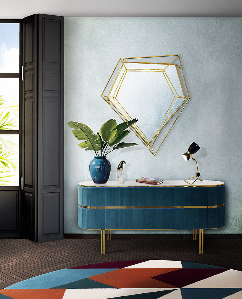 niebieska komoda ze złotymi elementami pod nietypową złotą ramką