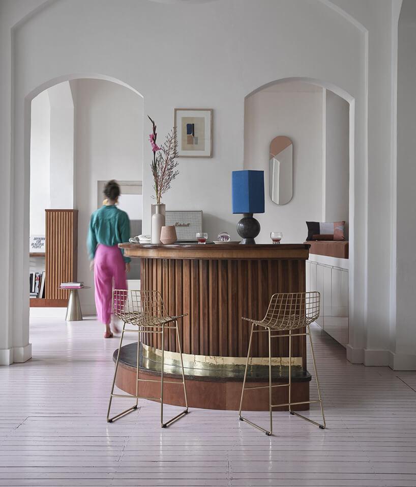 eleganckie białe wnętrze zdrewnianą wysoką wuspą idwoma złotymi wysokimi krzesłami