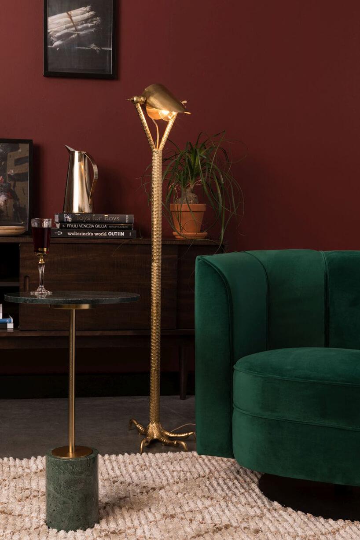 eleganckie wnętrze zzieloną sofą obok wysokiej złotej lampy podłogowej zpodstawową wkształcie szponów ptaka