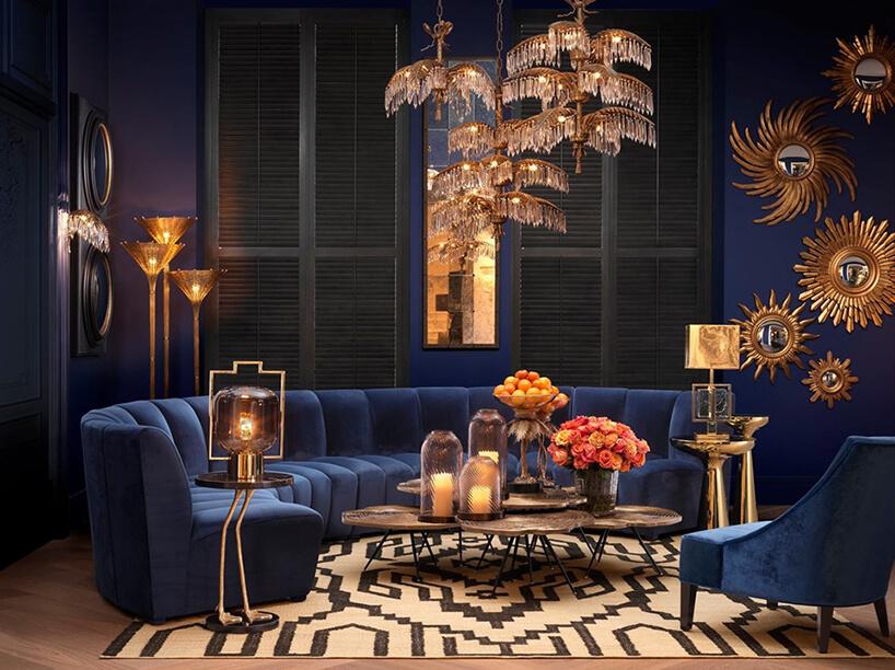 eleganckie ciemne wnętrze ze złotymi akcentami iniebieską sofą wcentrum salonu