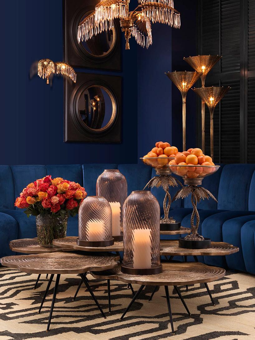eleganckie ciemne wnętrze zniebieskimi ścianami ze złotymi akcentami iniebieską sofą wcentrum salonu