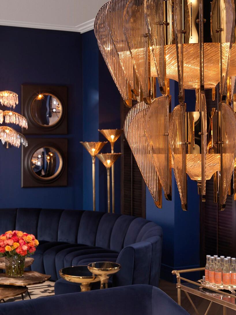 eleganckie ciemne wnętrze ze złotymi akcentami iniebieską sofą wcentrum salonu idużym złotym żyrandolem