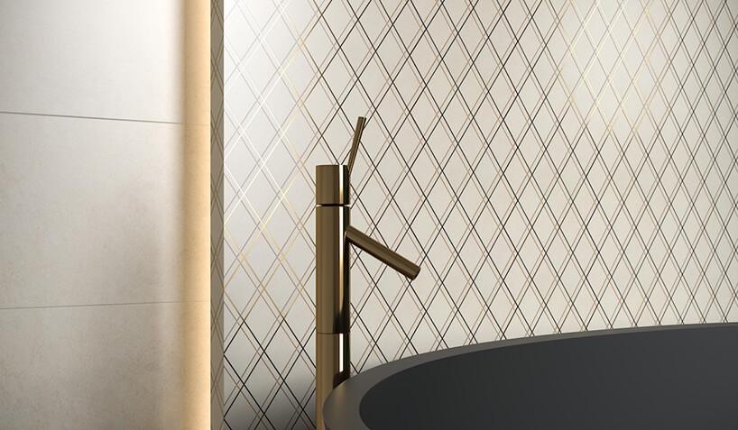 wysoka złota bateria wannowa na tle białej mozaik Arton od Paradyża ze złotą iczarną linią