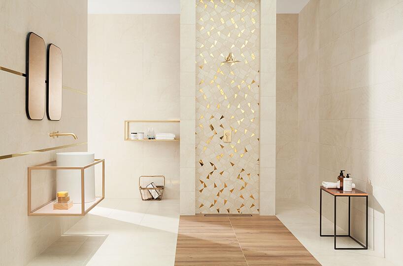 elegancka beżowa łazienka ze złotymi elementami icentralnym natryskiem ze ścianą wmozaikę Plain Stone do Ceramika Tubądzin ze złotymi elementami