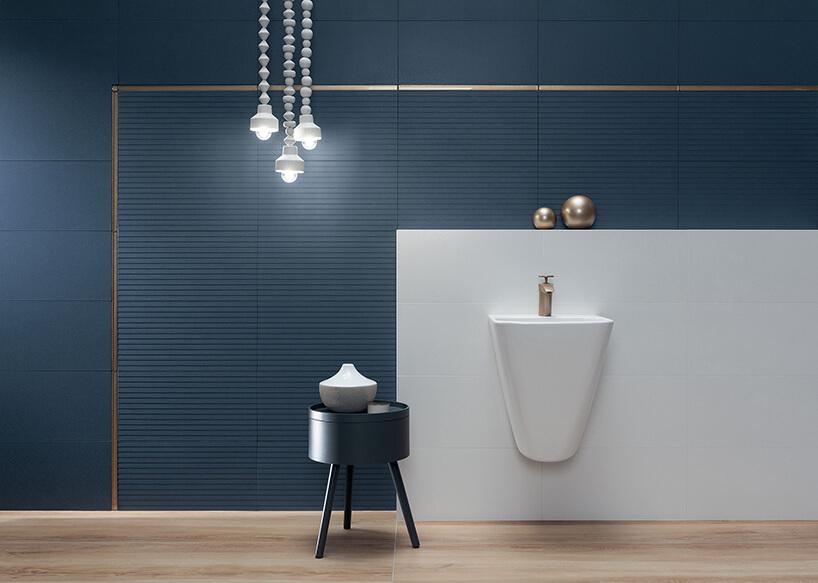 elegancka łazienka zdominującymi niebieskimi płytkami ze złotą wstawką obiałą wiszącą umywalką ze złotą armaturą