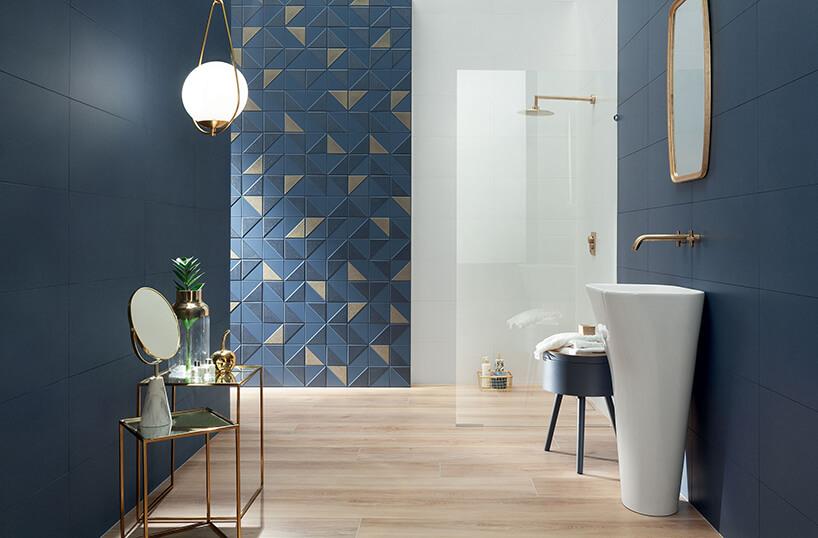 elegancka łazienka zniebieskimi ścianami zpłytek ze złotymi akcentami zoddzielonym szybą natryskiem