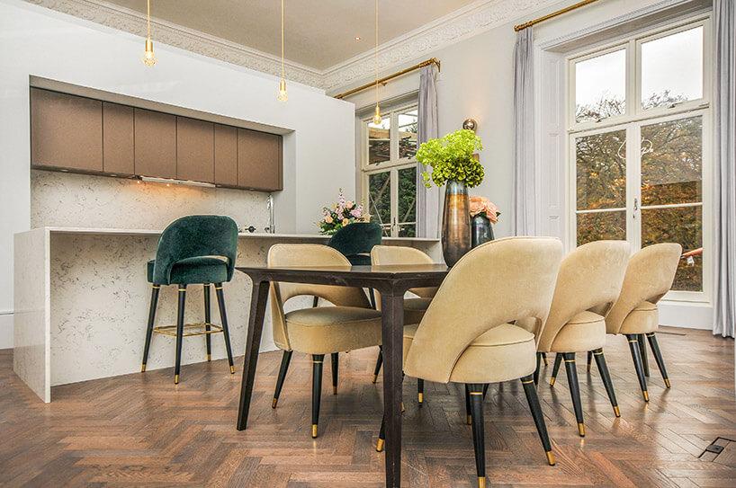 fotele przy stole wekskluzywnej jadalni połączonej zkuchnią