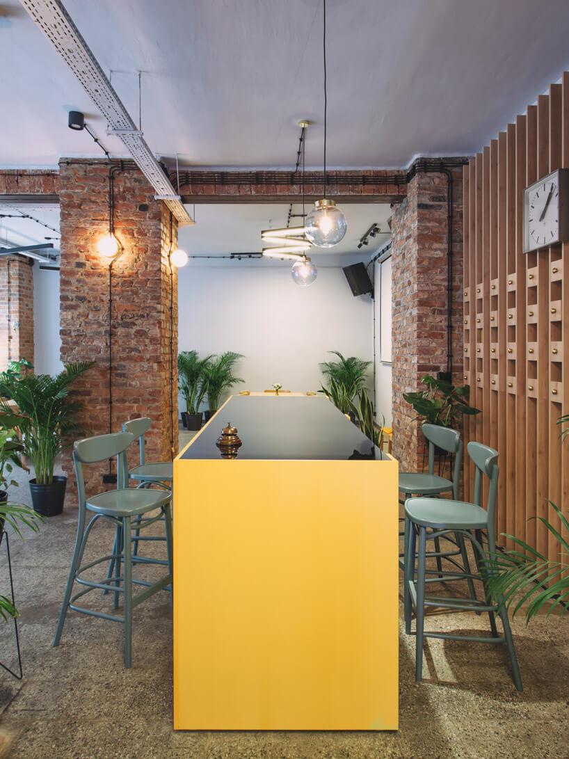 żółty stół zdużą szybą ikrzesłami barowymi