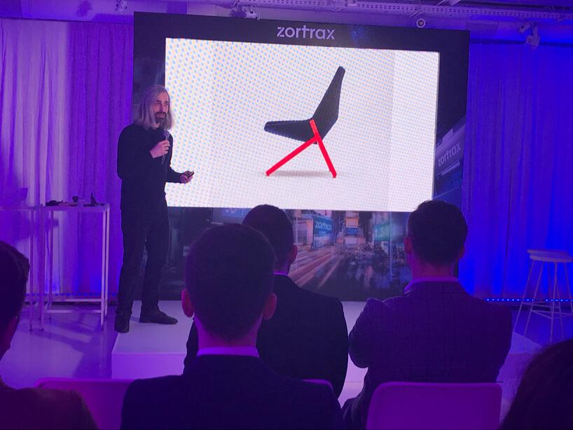 mężczyzna podczas prezentacji na tle slajdu zkrzesłem