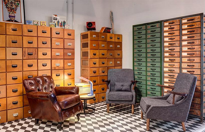 trzy stare fotele pośród szafek zbiblioteki