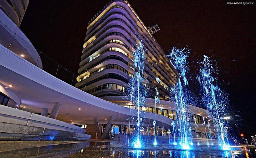 Fontanna nocą na tle oświetlonego hotelu